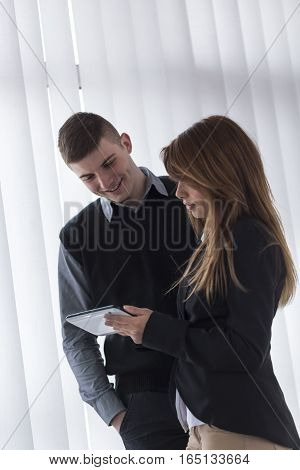 Two business people standing in an office and analyzing data on a tablet computer