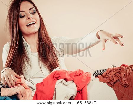 Young female behind sofa full of clothes. Woman with stretched arm grab try garment.
