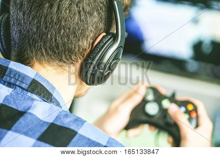 Video Gamer playing a videogame with joystick in his hands- A nerdy boy gaming online using new technology console on a big screen