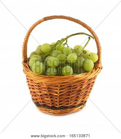Green grape bunch with ripe berries in small brown handmade wicker basket isolated over white close up