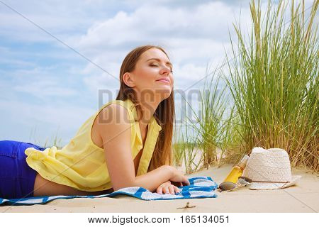 Young woman resting on summer beach. Pretty girl sunbathing on fresh air in summer.