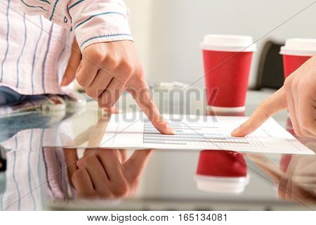 Detail of two business people's hands, pointing at success report, analyzing charts and graphs