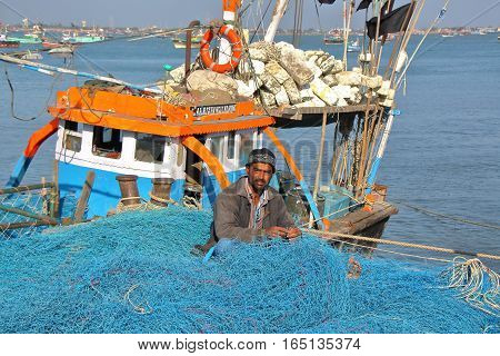 DWARKA, GUJARAT, INDIA - DECEMBER 26, 2013: Fisherman working on his fishing net in Bet Dwarka Island near Dwarka