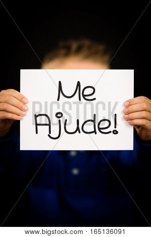 Studio shot of child holding a sign with Portuguese words Me Ajude - Help Me