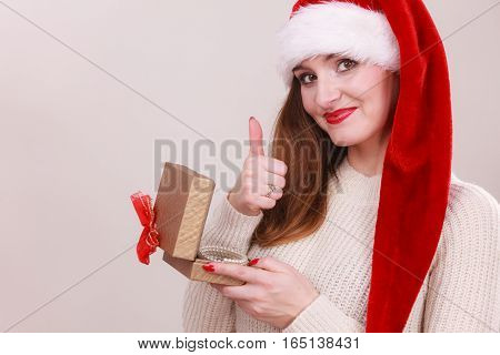 Young woman holding ribon box wearing santa cap. Celebration leisure relax holidays concept.