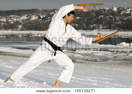 Ninja in white kimono is practicing with tonfa outdoors at winter barefoot in the snow.