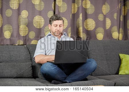Laptop And Man At Home On Sofa