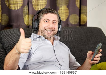 Man Thumbs Up With Headphones On Sofa