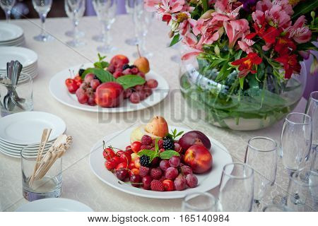 table with a white cloth covered with plates of fruit berries vase with flowers and glasses