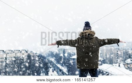 Teen looks into the distance standing on the edge of the rooftop