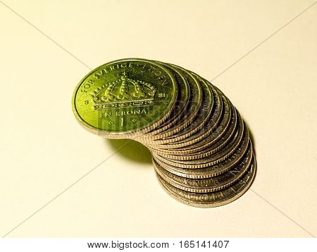 A pile of Swedish silver coins of one crown in green light