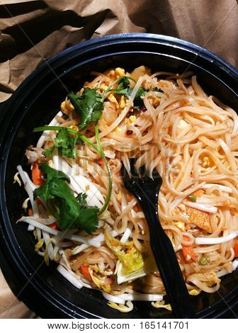 Take out fast food - noodles bowl with greens and vegetables. Quick tasty healty meal food from the local restaurant Top view