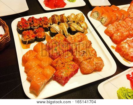 Dinner at  traditional Japanese sushi restaurant. Rolls with salmon fish, avocado, cream cheese, eel, masago, tamago, mussels with ginger and wasabi isolated on wooden table background