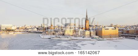 STOCKHOLM - JAN 08 2017: Panorama of Riddarholmen and Kunsholmen in central Stockholm with warm light a cold winter morning ice on the sea Malaren. January 08 2017 in Stockholm Sweden