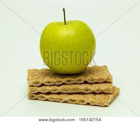 Green apple with crispbread on white background