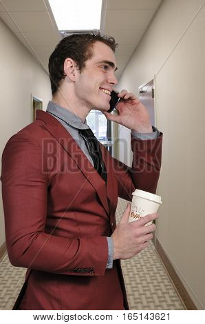 Handsome man using a cell phone will holding coffee