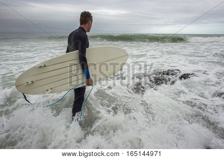 A surfer with wetsuit and surfboard under the arm enters the ocean in the surf.