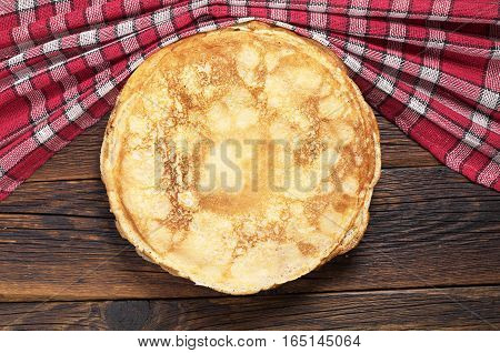Fried pancakes on rustic wooden table with tablecloth top view