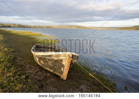 The hull of an old boat lies on the bank of a river.