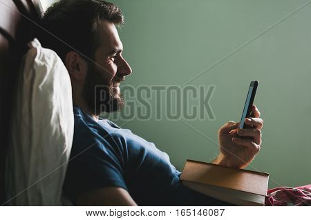 Young man lying in the bed with a book in his lap and a smartphone in his hand