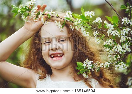Laughing toothless girl in white dress near blooming cherry trees. Happy healthy smile.