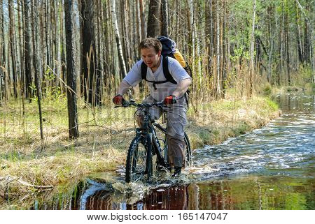 Mullashi, Russia - May 20, 2007: Man on bicycle goes along flooded road. Tyumen region