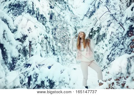 Beautiful girl smiling posing in a winter forest