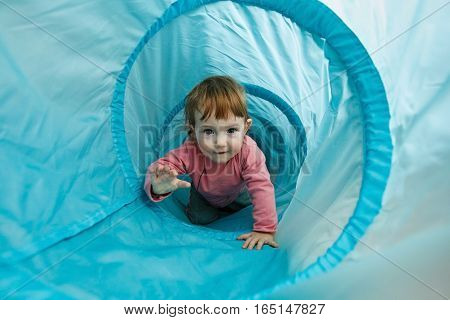 Small toddler playing in a tunnel tube crawling through it and having fun. Family fun early education and learning through experience concept.