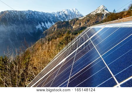 Closeup of photovoltaic solar panels in mountainous natural area gathering sunlight. Sustainable resources environmental conservation alternative power source and generation green energy concept.