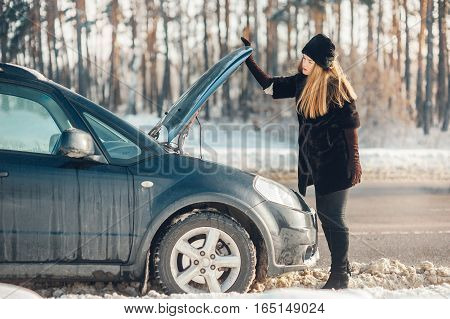 girl looks under cowl of broken car on rural road