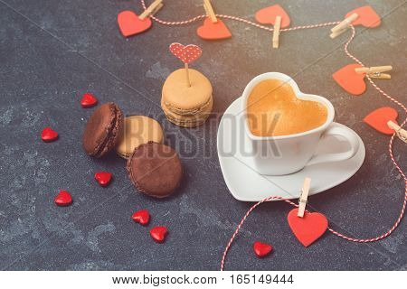 Valentines day concept with heart shape coffee cup and macarons over blackboard background