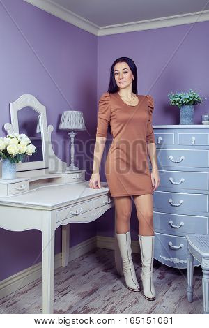 Beautiful woman with brown dress and long black hair in her room near her dressing table posing before party.