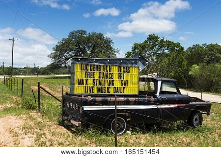 Luckenbach Texas USA - June 8 2014: Old truck with a sign for a music event in Luckenbach Texas USA.