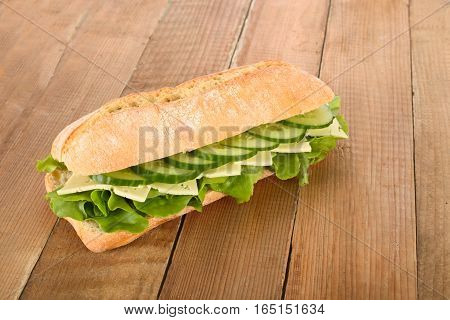 Fresh bread bun with cucumber slices, cheese and lettuce.
