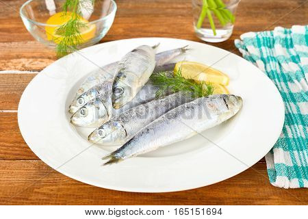 Frozen sardine fishes with lemon and dill on a white plate.