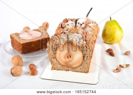 Homemade brown pound cake with whole pears and nut.