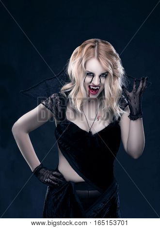 Beautiful blonde girl vampire wearing black clothes. The blood is on the mouth and eyes.