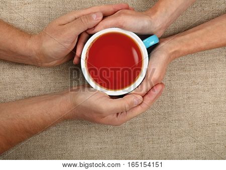 Man And Woman Hands Holding Full Black Tea Cup