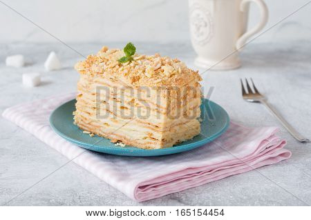 Piece of cake Napoleon on blue plate on pink textile. Russian cuisine, multi layered cake with pastry cream, close up view