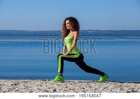 Young beautiful athletic woman with long curly hair in the morning runs on the beach by the lake. The concept of a healthy lifestyle and sports culture.