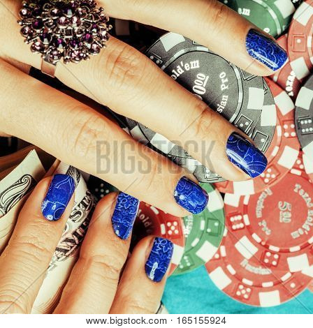 hands of young caucasian woman with blue manicure at casino table close up, deep indigo design on nails