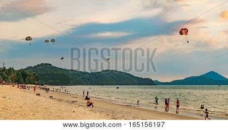 Langkawi, Malaysia - February 13, 2016: Paragliders at sunset summer adventure in Pantai Tengah Beach, Malaysia, Langkawi Island. Unidentified tourists take pictures and watch the colorful sunset.