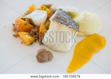 Sea Bass dill polenta cake sauteed courgette rocket and shellfish mayo on plate.