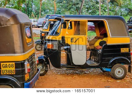 Goa, India - November 16, 2012: Parking of auto rickshaws. A tuk-tuk driver is taking a nap lying inside the car.