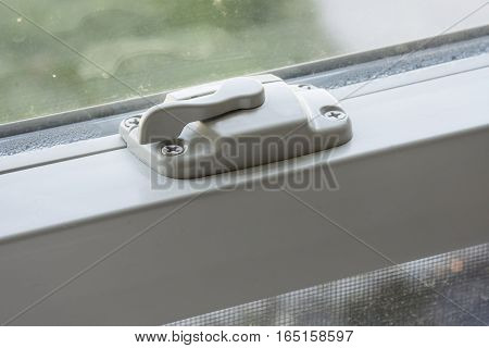 A lock or latch on a window in a home.