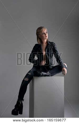 Beautiful young woman wearing leather jacket, jeans and boots on a high platform posing to camera on grey while sitting on cube.Rock or punk clothes style