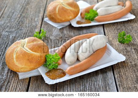 German street food: Bavarian white sausages and wieners with a fresh roll and sweet mustard on a paper plate