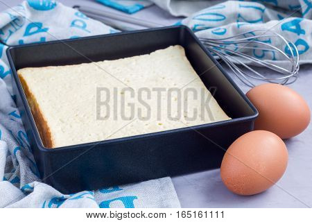 Homemade freshly baked square sponge cake in baking dish ingredients on background horizontal