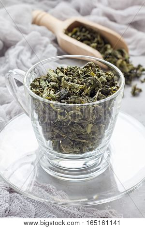 Dry green tea leaves in glass cup and on background vertical