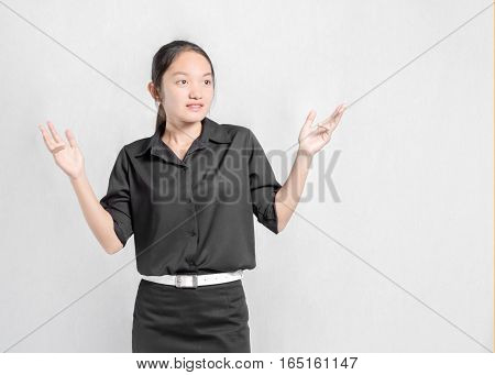 Portrait Of A Beautiful Asian Girl In A Pose I Do Not Know With Black Uniform. Isolated On Grey Back